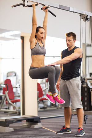 raises: sport, fitness, lifestyle, teamwork and people concept - young woman with trainer hanging on bar and doing leg raises in gym