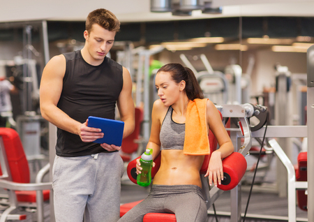 personal computer: fitness, sport, exercising, technology and people concept - smiling young woman and personal trainer with tablet pc computer in gym