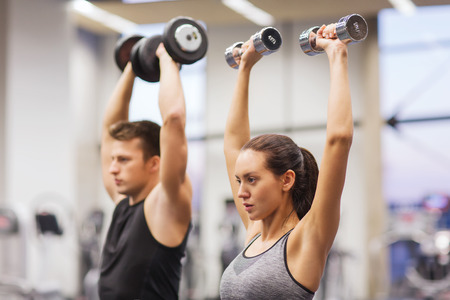 hand out: sport, fitness, lifestyle and people concept - smiling man and woman with dumbbells flexing muscles in gym