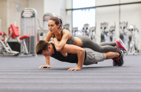 ups: fitness, sport, training, teamwork and lifestyle concept - smiling couple doing push-ups in the gym