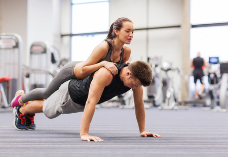 fitness, sport, training, teamwork and lifestyle concept - smiling couple doing push-ups in the gym photo