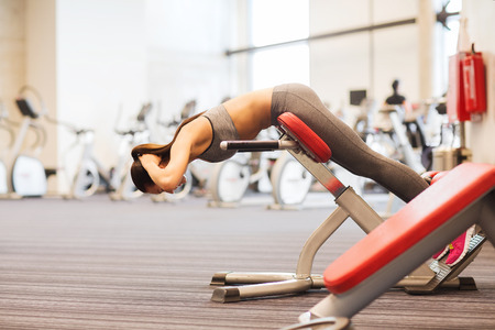 back training: sport, training, fitness, lifestyle and people concept - young woman flexing back muscles on bench in gym