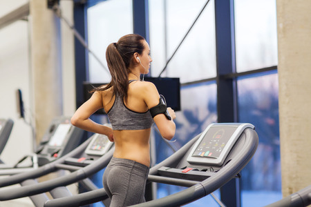exercise equipment: sport, fitness, lifestyle, technology and people concept - woman with smartphone or player and earphones exercising on treadmill in gym