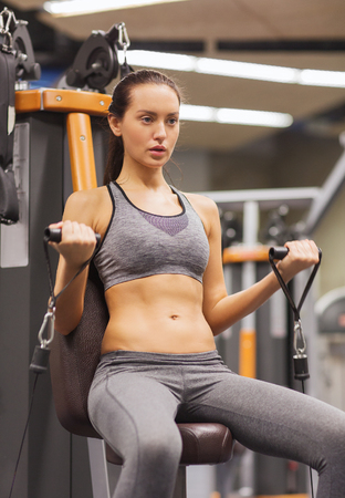 pull out: sport, fitness, lifestyle and people concept - young woman flexing muscles on gym machine Stock Photo