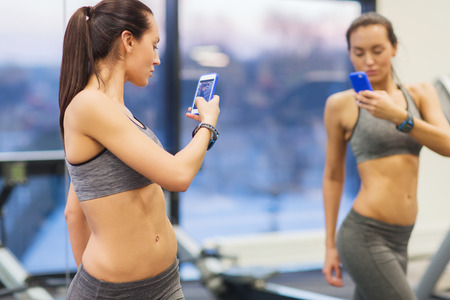 mirror: sport, fitness, lifestyle, technology and people concept - young woman with smartphone taking mirror selfie in gym