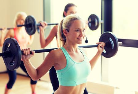 fitness, sport, opleiding en lifestyle-concept - groep van vrouwen met halters in sportschool