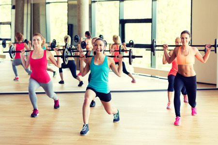 instructor: fitness, sport, training and lifestyle concept - group of women with barbells in gym
