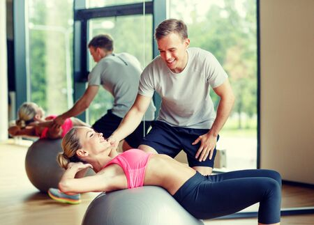 six packs: fitness, sport, exercising and diet concept - smiling young woman and personal trainer in gym Stock Photo