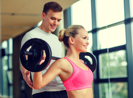 sport, fitness, lifestyle and people concept - smiling man and woman with barbell exercising in gym Foto de archivo
