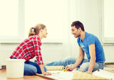 repair, building and home concept - smiling couple measuring wallpaper photo