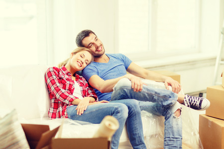 home moving: moving, home and couple concept - smiling couple relaxing on sofa in new home Stock Photo