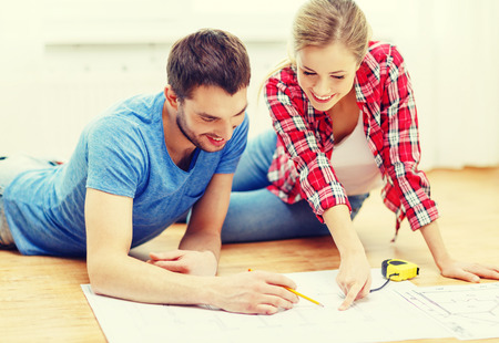new homes: repair, building, renovation and home concept - smiling couple looking at blueprint at home