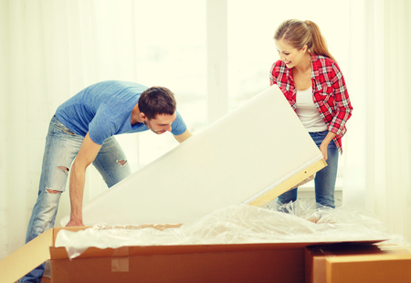 moving activity: repair, building and home concept - smiling couple opening big cardboard box with sofa