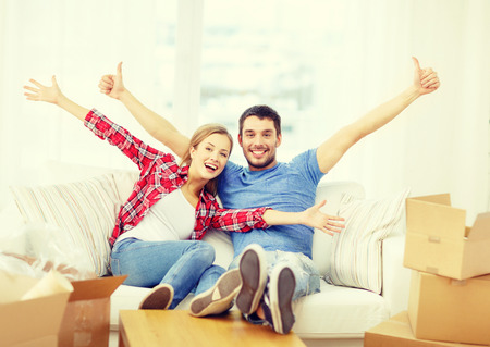 first home: moving, home and couple concept - smiling couple relaxing on sofa in new home Stock Photo
