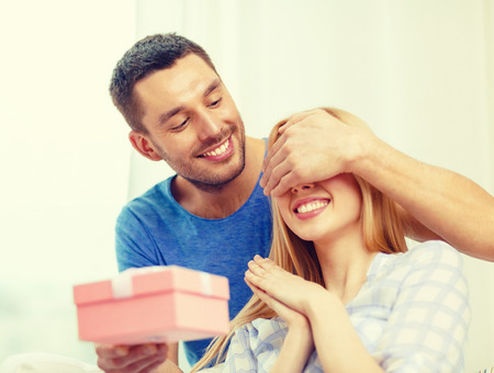 presents: love, holiday, celebration and family concept - smiling man surprises his girlfriend with present at home