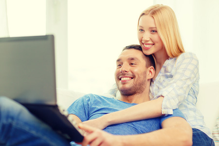 love, family, technology, internet and happiness concept - smiling happy couple witl laptop computer at home photo