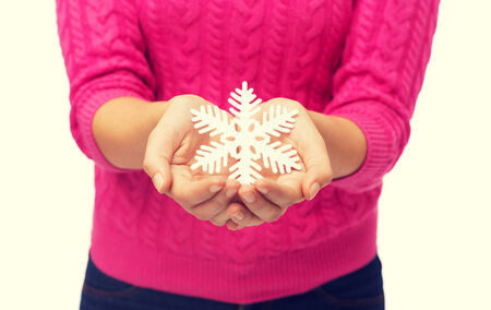 christmas, holidays and people concept - close up of woman in pink sweater holding snowflake photo