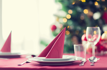 red green: holidays, celebration and home concept - close up of room with christmas tree and decorated table