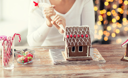 holiday cookies: cooking, people, christmas and decoration concept - close up of happy woman making gingerbread houses at home