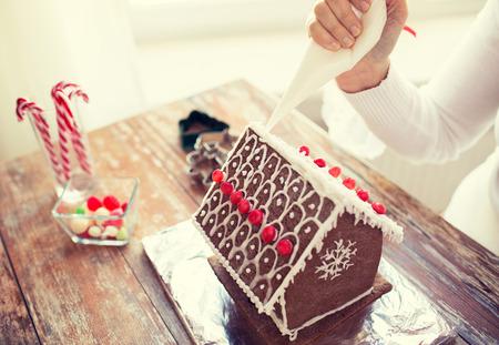cake decorating: la cocina, la gente, la Navidad y la decoraci�n concepto - cerca de feliz mujer haciendo casas de jengibre en casa