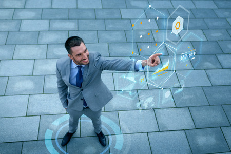 business, development, technology and people and concept - young smiling businessman pointing finger to virtual screens with graphs outdoors from top