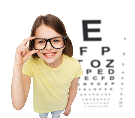 teenage problems: people, childhood, healthcare and vision concept - smiling little girl in black eyeglasses over white background with eye chart Stock Photo