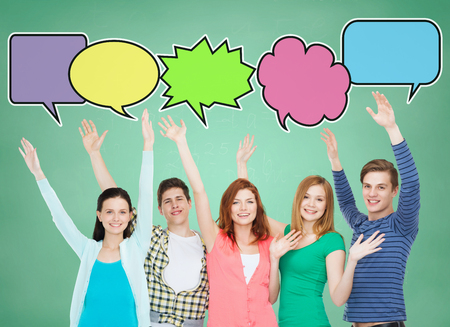 school, education, communication, gesture and people concept - group of smiling teenagers waving hands over green board background with text bubbles photo