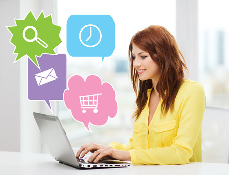 online: people, technology and internet concept - smiling woman sitting on couch with laptop computer at home with internet icons
