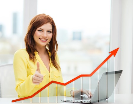 people, technology, statistic sand business concept - smiling woman with laptop computer and growth chart showing thumbs up at home Foto de archivo