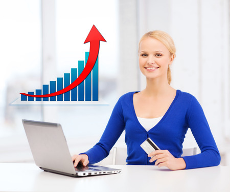 online shopping, finances, people and technology concept - smiling young woman with laptop computer, credit card and growth chart photo