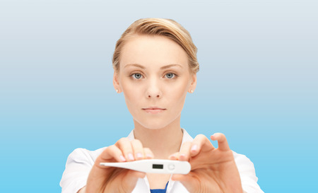 medicine, people, equipment and healthcare concept - young female doctor showing thermometer over blue background photo