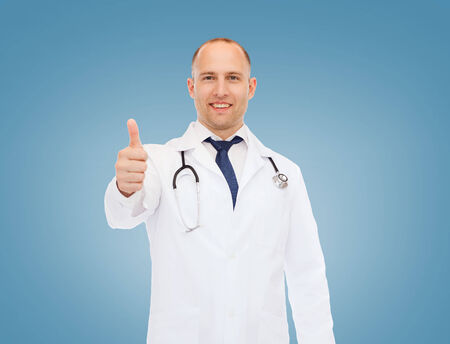 approvement: healthcare, profession, gesture and medicine concept - smiling male doctor with stethoscope showing thumbs up over blue background