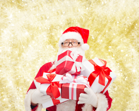 st nick: christmas, holidays and people concept - man in costume of santa claus with gift boxes over yellow lights background