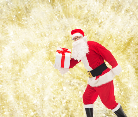 st nick: christmas, holidays and people concept - man in costume of santa claus running with gift box over yellow lights background