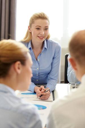 papeles oficina: negocio, la gente y el trabajo en equipo concepto - sonriendo equipo de negocios con papeles reuni�n en la oficina Foto de archivo