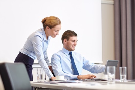 to the secretary: business, people and work concept - businessman and secretary with laptop working in office Stock Photo