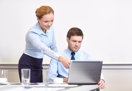 career young: business, people and work concept - businessman and secretary with laptop working in office Stock Photo