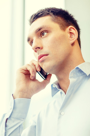 business, technology and office concept - serious businessman with smartphone photo