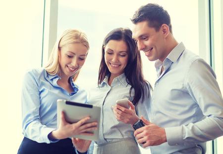 zakelijke en office concept - lachende business team werken met tablet-pc's en smartphones in het kantoor