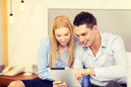 business, hotel, trave and technology concept - smiling couple with tablet pc computer in hotel room
