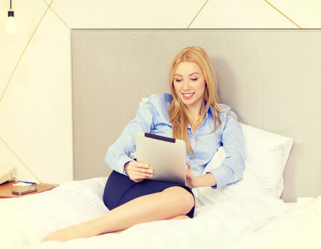 charming business lady: business, technology, internet and hotel concept - happy businesswoman with tablet pc computer lying in hotel in bed