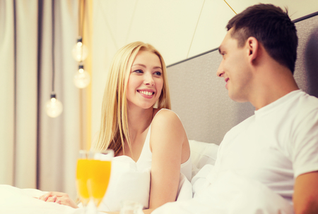 hotel, travel, relationships and happiness concept - smiling couple having breakfast in bed in hotel room photo
