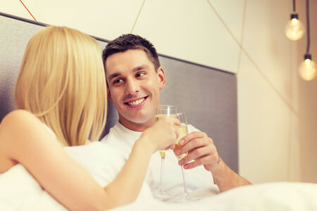 hotel, travel, relationships and happiness concept - smiling couple with champagne glasses in bed photo