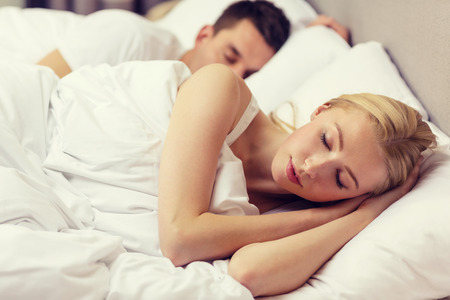 romance bed: hotel, travel, relationships, and happiness concept - happy couple sleeping in bed