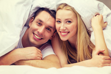 hotel, travel, relationships, and happiness concept - happy couple in bed Stock Photo