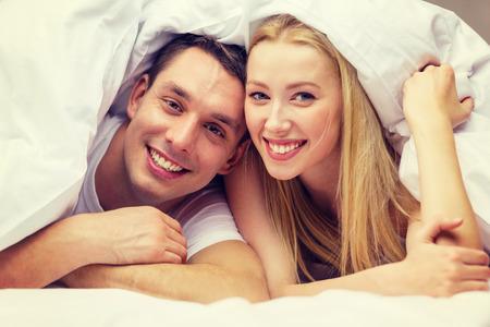 hoteles, viajes, relaciones, felicidad y concepto - pareja feliz en la cama