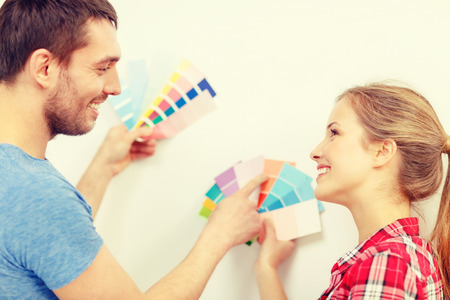 refurbish: repair, interior design, building, renovation and home concept - smiling couple looking at color samples at home