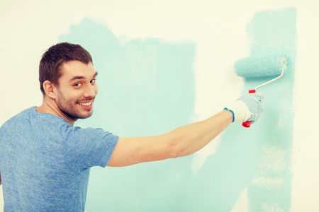 man painting: repair, building and home concept - smiling man painting wall at home