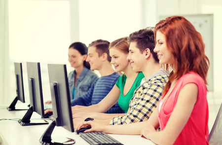 college education: education, technology and school concept - smiling female student with classmates in computer class at school