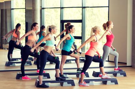 aerobics: fitness, deporte, entrenamiento, gimnasio y estilo de vida concepto - grupo de mujeres de trabajo con pesas en el gimnasio y steppers